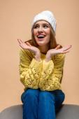 bella donna positiva in maglione giallo e cappello seduto sulla poltrona, isolato sul beige