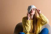 attractive woman in yellow sweater and hat making air kiss while sitting in armchair on beige