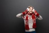 krásná vzrušená žena ve vánočním svetru, šála, palčáky a chrániče sluchu, izolovaná na šedi