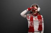 attraktive glückliche Frau in Weihnachtspullover, Schal, Handschuhe und Ohrenschützer, isoliert auf grau