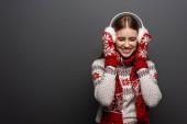 vonzó nevető nő karácsonyi pulóver, sál, kesztyű és fülvédő, elszigetelt szürke