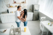 happy pregnant family hugging in kitchen with orange juice