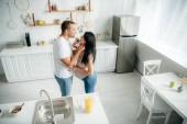 šťastný těhotná rodina objímání v kuchyni s pomerančovým džusem