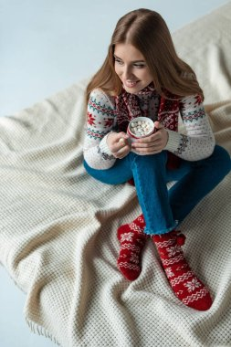 happy woman in warm sweater holding cup of cocoa with marshmallow and sitting on blanket