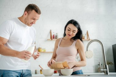 Happy pregnant couple making cereals with milk in kitchen stock vector