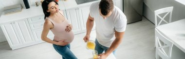 panoramic shot of beautiful smiling pregnant wife in kitchen with husband pouring orange juice