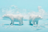 Two toy polar bears with polyethylene trash on blue background, animal welfare concept