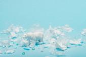 Fotografie weißer Spielzeug-Eisbär mit Plastikmüll auf blauem Hintergrund, Tierschutzkonzept