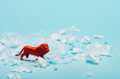 Red toy lion with plastic pieces on blue background, environmental pollution concept