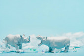 Fotografie White hippopotamus and rhinoceros toys with plastic garbage on blue background, animal welfare concept