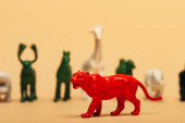 Selective focus of red tiger with colored toy animals on yellow background, extinction of animals concept