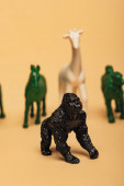 Photo Selective focus of gorilla with colored toy animals on yellow background, extinction of animals concept