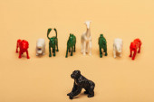 Selective focus of gorilla with colored toy animals on yellow background, extinction of animals concept