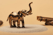 Selective focus of toy elephant on sand with stones and wooden sticks on yellow background, animal welfare concept
