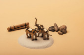Toy elephants on sand with stones and wooden sticks on yellow background, animal welfare concept