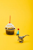 Toy dinosaur in party cap and cupcake with candle on yellow background