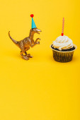 Toy dinosaur in party cap beside cupcake with candle on yellow background