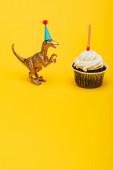Toy dinoszaurusz party sapka mellett cupcake gyertya sárga háttér