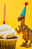 Selective focus of toy dinosaur in party cap beside cupcake with candle on yellow background