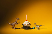 Fényképek Toy dinosaurs with party cap beside cupcake with candle on orange background
