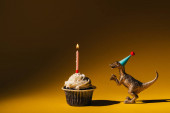 Toy dinosaur in party cap beside cupcake with burning candle on brown background