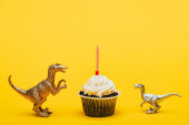 Toy dinosaurs beside cupcake with candle on yellow background