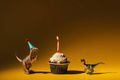 Toy dinosaurs with party cap and cupcake with burning candle on orange background