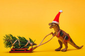 Photo Toy dinosaur in santa hat with pine on sleigh on yellow background