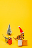 Toy dinosaurs in santa hat with shopping bags and christmas tree on yellow background