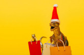 Selective focus of toy dinosaurs in santa hat and shopping bags on yellow background