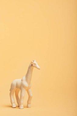 White toy giraffe on yellow background, animal welfare concept stock vector