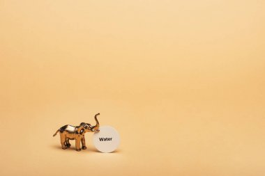 Golden toy elephant with lettering water on card on yellow background, water scarcity concept stock vector
