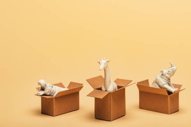 White toy hippopotamus, rhinoceros and giraffe in cardboard boxes on yellow background, animal welfare concept stock vector