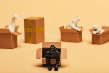 Selective focus of animal toys in cardboard boxes on yellow background, animal welfare concept stock vector