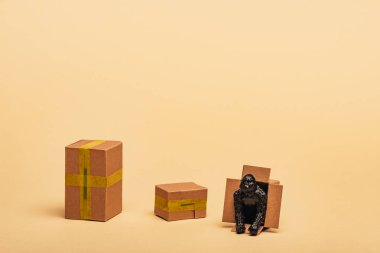 Toy gorilla in cardboard container with boxes on yellow background, animal welfare concept stock vector