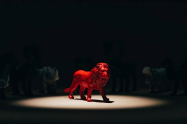 Red toy lion under spotlight with animals at background, voting concept