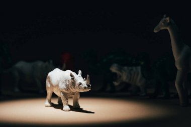 White toy rhinoceros under spotlight with animals at background, voting concept