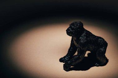 Toy gorilla under spotlight on black background
