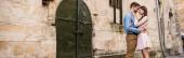 colpo panoramico di giovane coppia abbracciare mentre in piedi vicino vecchio castello in pietra