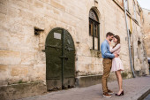 coppia di giovani turisti che abbracciano mentre in piedi vicino vecchio castello in pietra