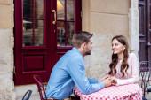šťastný mladý pár drží za ruce a dívá se na sebe, zatímco sedí v kavárně