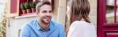 panoramatický snímek mladého muže usmívajícího se při pohledu na přítelkyni