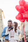 boldog lány csók mosolygós barátja, miközben a kezében piros szív alakú lufik az utcán