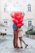 happy young couple embracing while hiding behind red heart-shaped balloons on city square