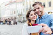 selektivní zaměření usměvaví turisté brát selfie s smartphonem na ulici
