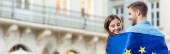 panoramatický záběr mladých, usmívajících se turistů obtékajících vlajku Evropské unie na ulici