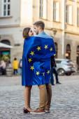šťastní turisté, zabaleni v vlajce Evropské unie, hledící jeden na druhého na ulici