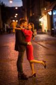 šťastná, elegantní dívka drží kytice růží při objímání přítele v noci ulici