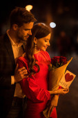 handsome man hugging happy girlfriend holding bouquet of roses and card with love inscription and heart symbol