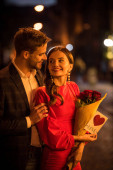 smiling man hugging happy girlfriend holding bouquet of roses and card with love inscription and heart symbol